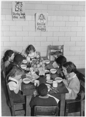 Seven children, ages 7-9, sit around a table, with hands folded in prayer. Bowls, cups and plates are on the table in front of them.