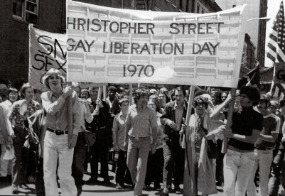 Photo of a large group of people marching holding a large banner the read: Christopher Street Gay Liberation Day 1970
