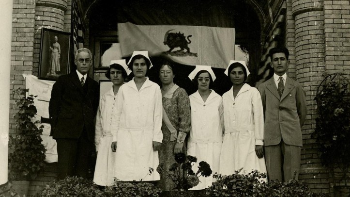 A black-and-white group portrait taken under an arched doorway featuring two men in suits and women in doctor coats
