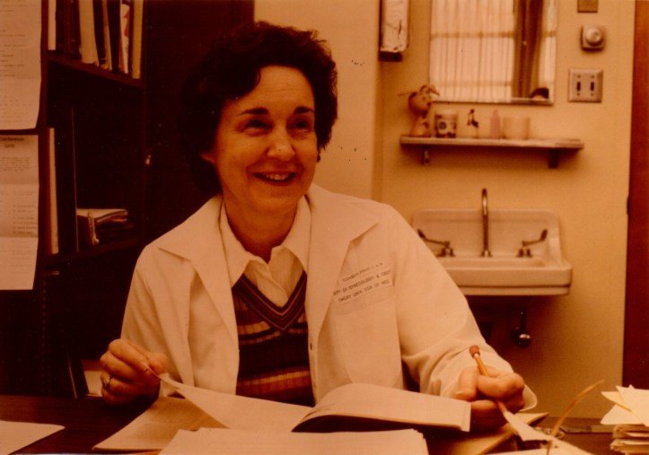 Photo of a smiling woman with dark hair and a lab coat seated at a desk