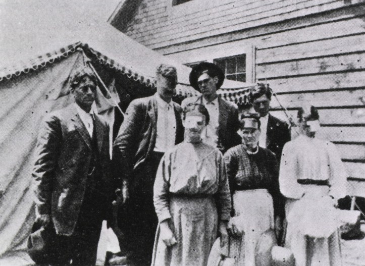 Several people, some wearing eye bandages, standing in front of a tent, a wooden building is in the background