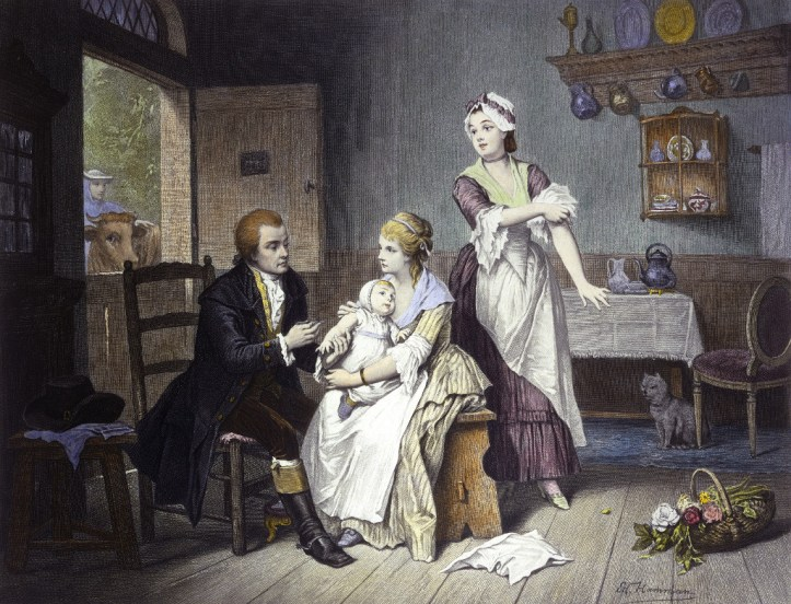 Edward Jenner, vaccinating his young child, held by Mrs Jenner; a maid rolls up her sleeve, a man stands outside holding a cow. Coloured engraving by C. Manigaud after E Hamman