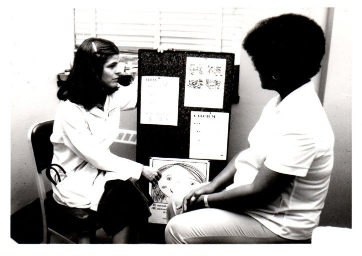 Black and white photo of a nurse-midwife seated indicating a poster display talking to another seated person