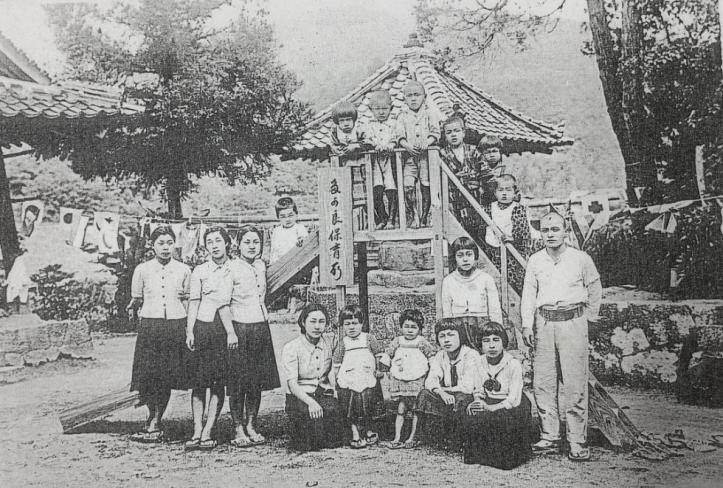 Black and white photo of adults and children lined up in front of a gazebo for a formal portrait