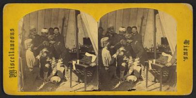Seven men surround and tend to one wounded soldier in a cramped tent space.