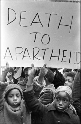 Two black children hold up a sign that reads DEATH TO APARTHEID.