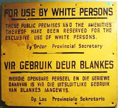 Yellow sign with words written in black, both in English and in Dutch. English reads: FOR USE BY WHITE PERSONS. THESE PUBLIC PREMISES AND AMENITIES THEREOF HAVE BEEN RESERVED FOR THE EXCLUSIVE USE OF WHITE PERSONS. By order of the Provincial Secretary.