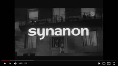 "The front of a building, with ""Syanon"" written superimposed over it."