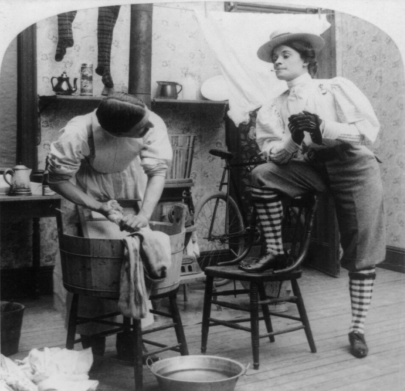 A woman dressed in pants and smoking has her boot up on a chair while a man bends over a wash tub scrubbing clothes.