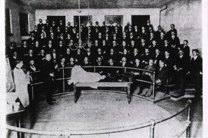 An amphitheater of young men look on as a teacher (doctor) approaches a table with a woman-shaped figure lying on her back with her knees up.
