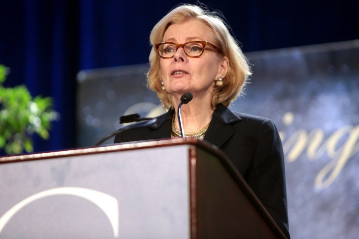 An older white woman with short blonde hair and black glasses stands at a podium.