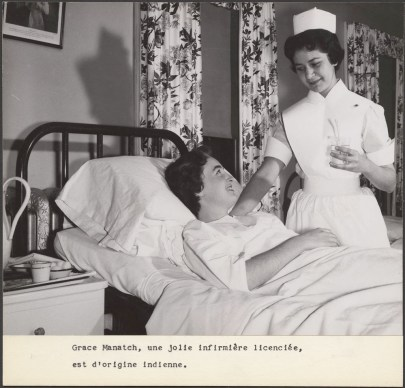 An indigenous woman in a nurses uniform stands over a patient in a hospital bed.