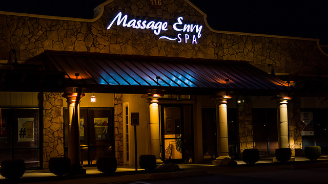 Photo of the front of a Massage Envy store front at night. A neon Massage Envy sign is lit up over a red awning