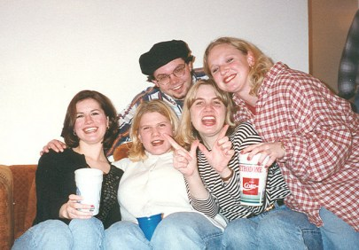 Four white women and one white man sit together on a couch. Two women hold big cups, possibly of soda.