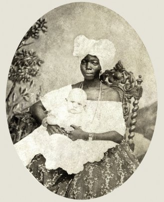 A black nanny with a white child.
