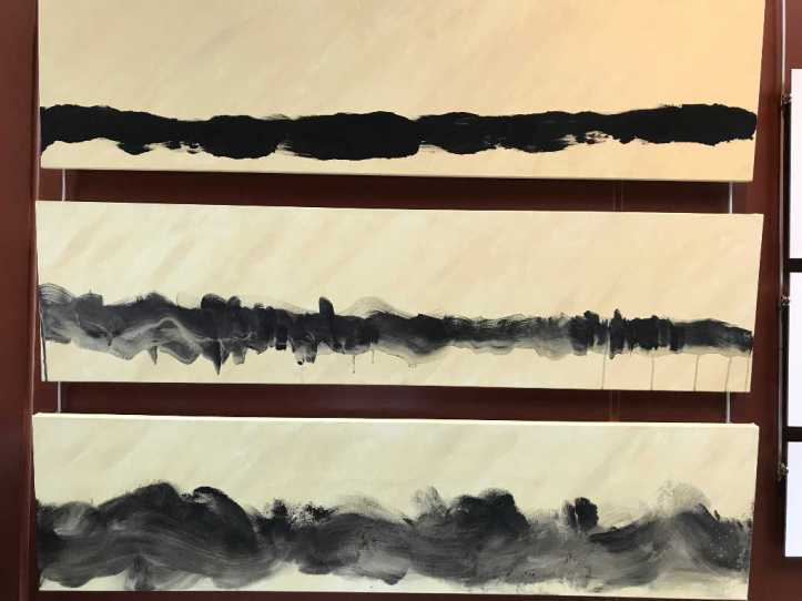 "Photo of three canvases lined up, with a black line of paint from one side to the other on each canvas. From top to bottom, the first canvas, ""Comfortably Numb,"" is the most linear and clear, painted while medicated. The second, ""Me and My Shadow,"" is similar, yet slightly smudged and painted while enduring nerve pain. The third, ""The Fix is In,"" is smudged even further, and was painted while ""self-medicated."""