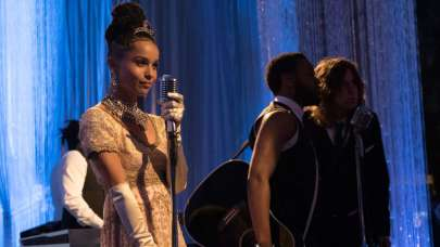 Zoe Kravitz wears a silvery gown and tiara and sings into an old fashioned mic.