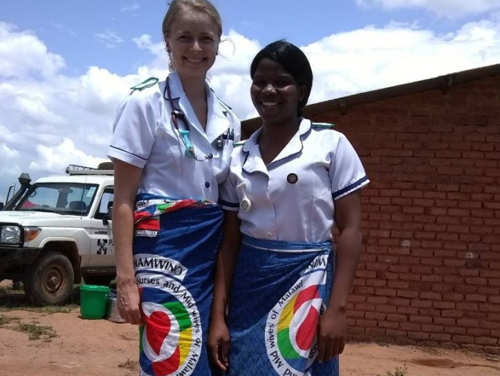 Photo of two women standing next to each other outside with Nurses and Midwives of Maliwai wraps