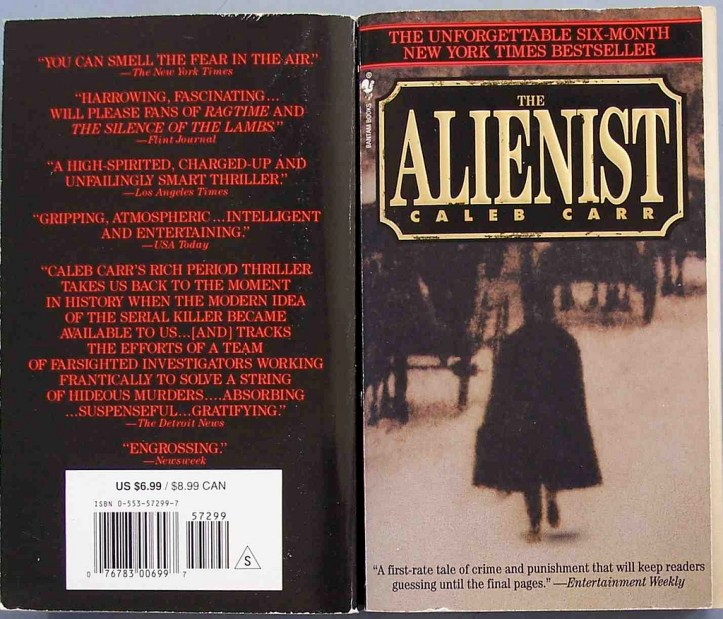 Book jacket features a blurry photo of a man in a long black trench coat or cape walking by some carriages being pulled by horses. The Alienist is written across the top in yellow lettering.