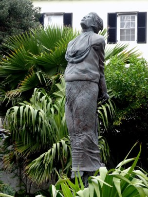 Photo of a gray monument of a woman in flowing clothes tied to a stake with her hands behind her back with her face turn up towards the sky and her eyes closed.
