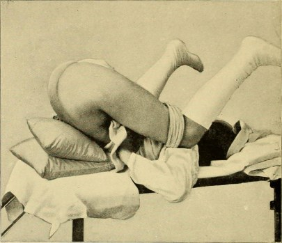A woman is lying on her back with her legs thrown behind her head.