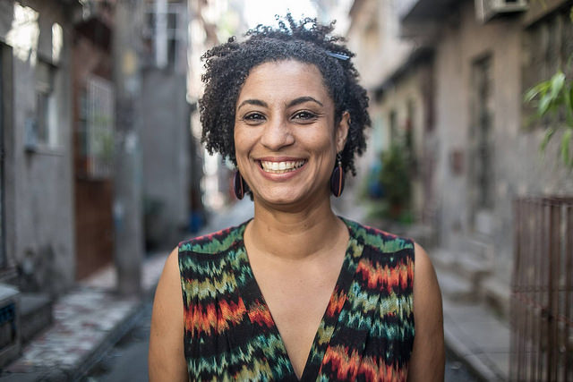 Photograph of a smiling woman with short dark hair. She is standing is a street. She is Marielle Franco.