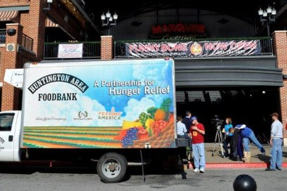 "Photo of a delivery truck with ""Food Bank"" and other graphics on the side. Some people move a pallet of food stuffs nearby."