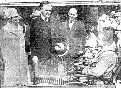 President Calvin Coolidge in the center of a group of people. Coolidge is slightly smiling down at a smiling man in a wheelchair.