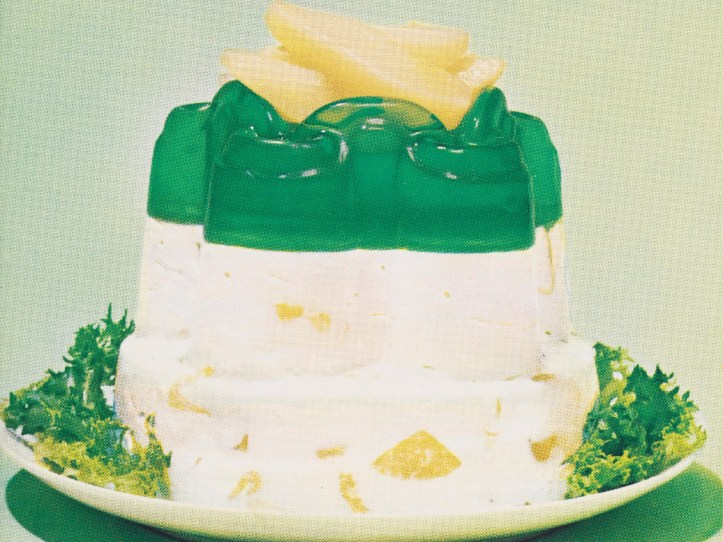 A page from a cookbook showing a recipe for a Jello-O salad including ingredients such as pear halves, cream cheese, and ginger. The image of the finished salad is a tall column-like shape which is white on the bottom with green jello on top, topped with pear halves.