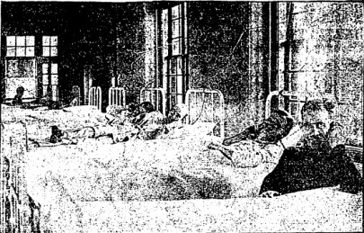 A 1923 hospital ward with people laying in side-by-side and a man in the foreground holding a radio receiver to his ear.