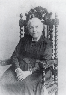 Harriet Jacobs sits for a portrait in a fancy wooden chair. She is advanced in years in this photo.