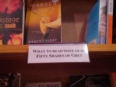 A sign on a bookshelf says What to read instead of 50 shades of grey.