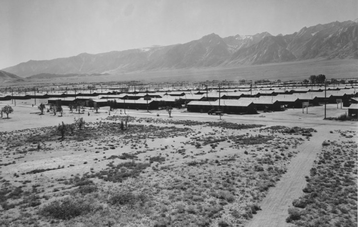 A panoramic desert landscape with a lot of sand, mountains in the background, and long rows of military style barracks.