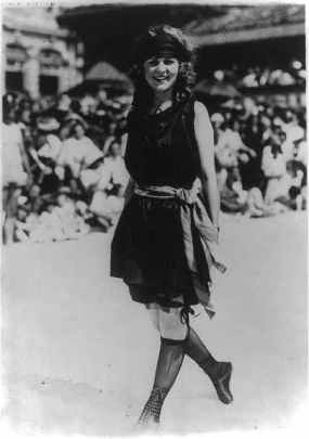 A woman standing, smiling and facing front with one foot pointed behind her, wearing a bathing suit in 1921.