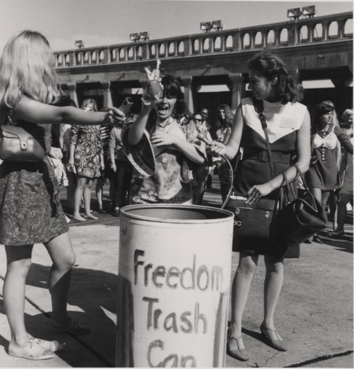 """Two women toss items into a trash can labeled """"Freedom Trash Can"""" while a woman reporter looks on."""