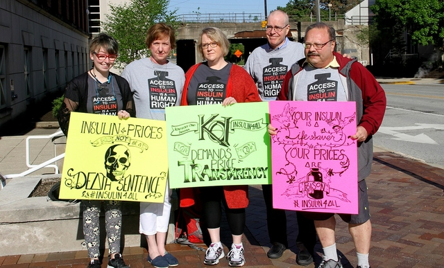 "Four people with matching t-shirts that read ""Access to insulin is a human right"" hold protest signs such as ""Insulin prices should not be a death sentence #insulin4all"""