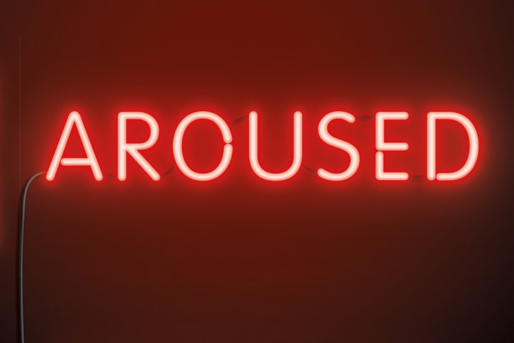 """Detail of a book cover showing red glowing neon lettering saying: """"Aroused"""" in all capital letters."""