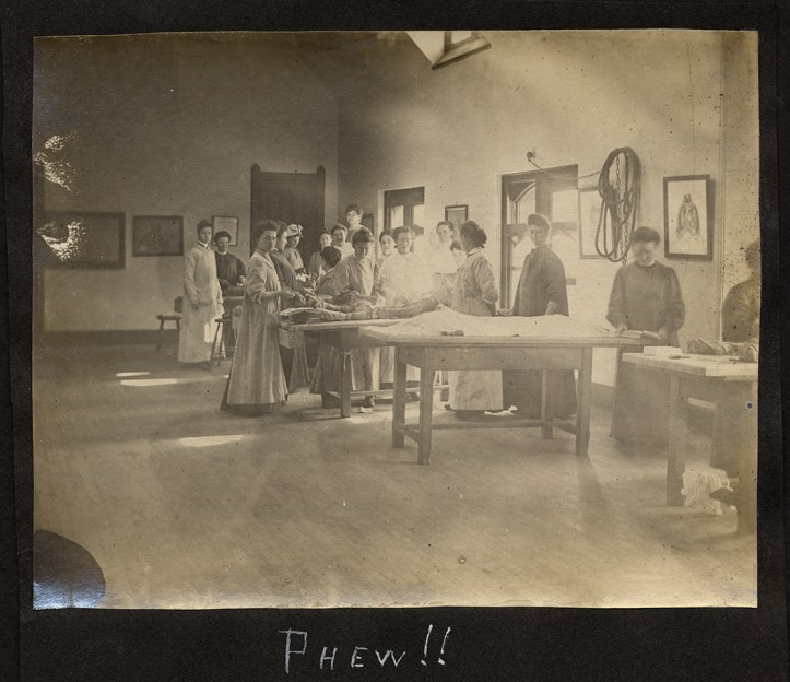 "A large room with a bare floor and a series of wooden operating with cadavers on them, surrounded by women in surgical gowns. In the photo caption someone wrote: ""Phew!"""