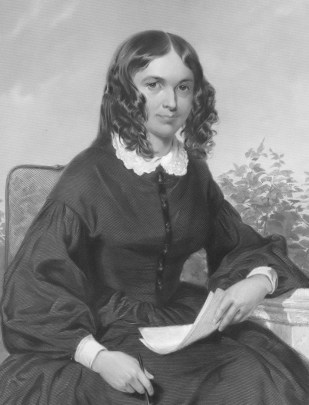 Elizabeth Barrett Browning seated at a desk holding papers. Her hair is in intense ringlet curls.