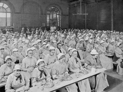 Hundreds of women seated closely together at narrow tables, wearing the same uniform of a pale colored rough-spun dress and white bonnet, eating.