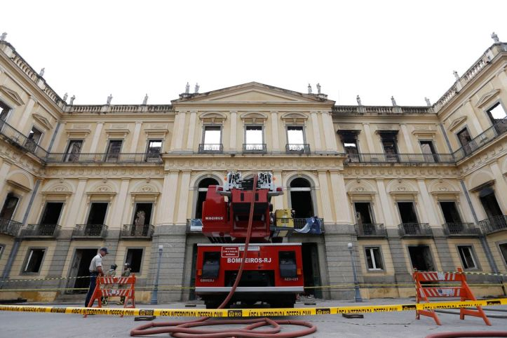 The three-story facade of Brazil's National Musueum, the interior is visibly missing and collapsed with smoke-stained windows. A red fire engine and police tape cross the foreground.