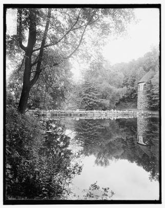 A reflective lake surrounded by tall trees and a rock wall and rock-sided building.