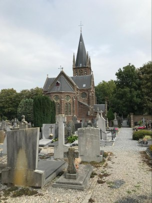 A brick church with a tall spire clocktower with a gravel graveyard in the foreground.
