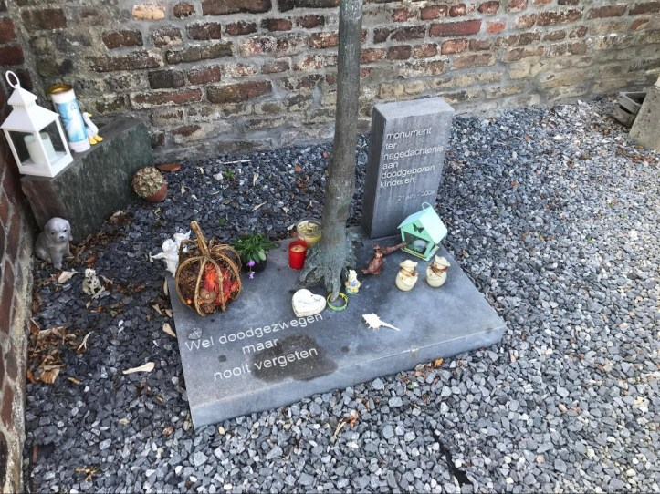 A gravel section in the corner of a brick wall with a small tree on top of a concrete slab arrayed with small items and candles.