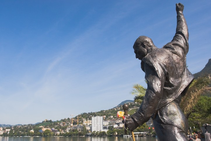Bronze statue of Freddy Mercury looking out on an ocean bay.