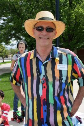A smiling man in sunglasses and a straw hat wearing a colorful striped shirt.