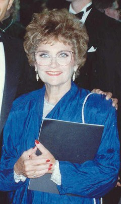 A smiling woman with short curly brown hair wearing classes and a blue shirt.