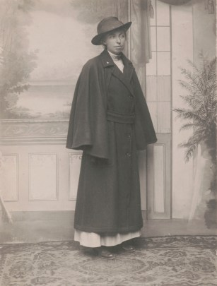 Old black-and-white photo of a standing young woman in a wide-brimmed hat and a large coat that conceals her hands.