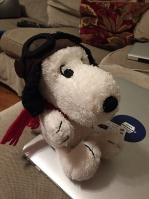 Snoopy plushie in an aviatory helmet sitting on a laptop.