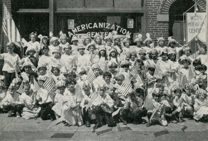 A large crowd of people sitting for a group portrait all holding American flags.